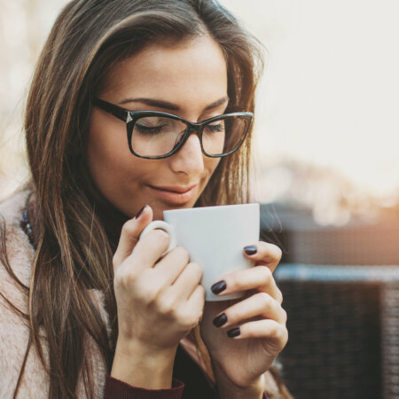 Young woman holding a cup of coffee, taking the aroma, with copy space